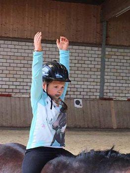 Kind bei ZENbo Balance Übung auf dem Pferd